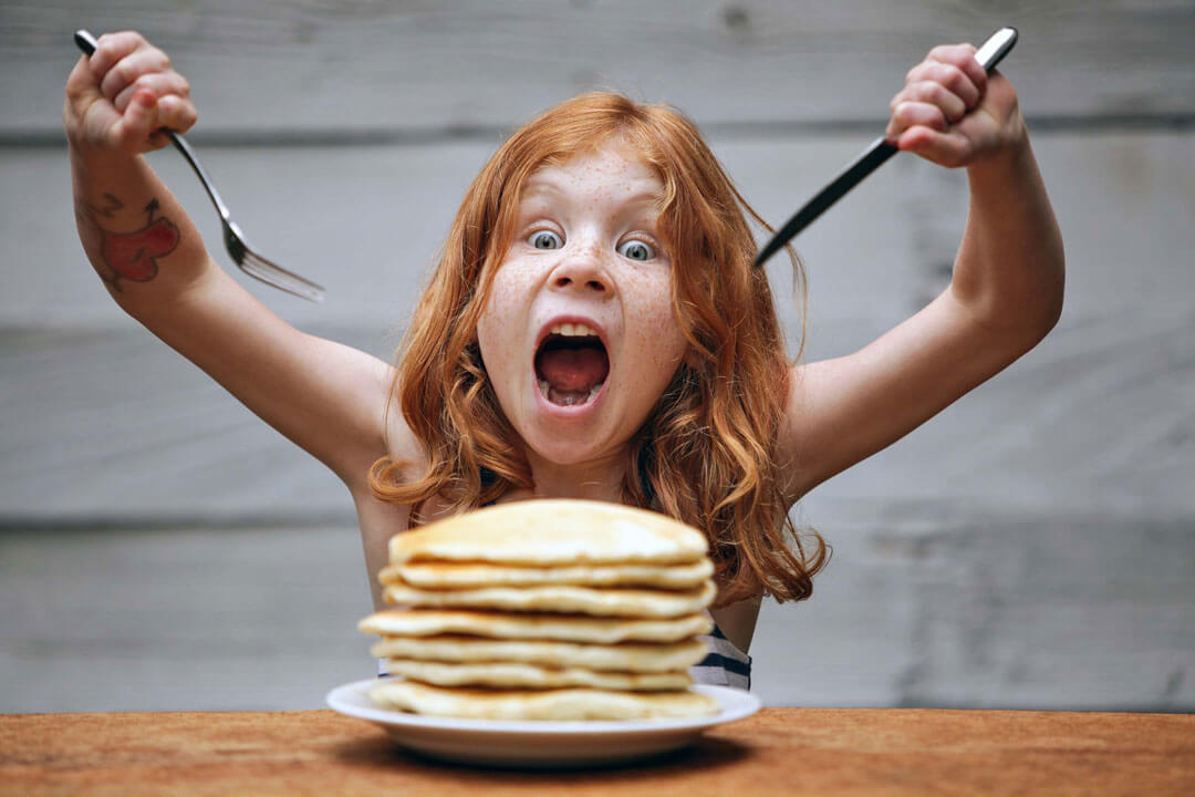 Girl enthusiastically eating a stack of pancakes